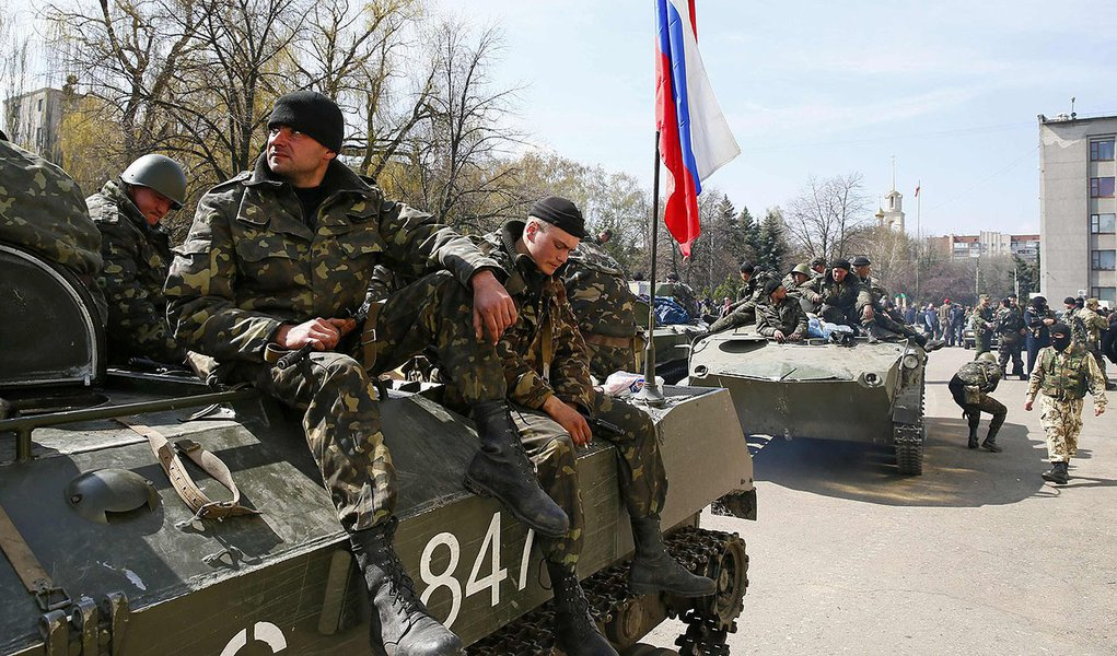 Armed men sit on an armoured personnel carrier with a Russian flag on it in Slaviansk April 16, 2014. Six armoured troop carriers entered the eastern Ukrainian town of Slaviansk on Wednesday carrying the Russian national flag and the banner of pro-Russian