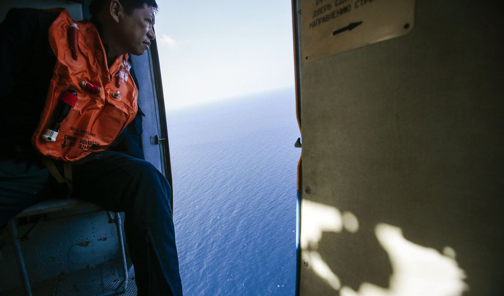 "A military personnel looks out of a helicopter during a search and rescue mission off Vietnam's Tho Chu island March 10, 2014. The disappearance of Malaysia Airlines flight MH370, a Boeing 777-200ER jetliner, is an ""unprecedented mystery"", the country's c"