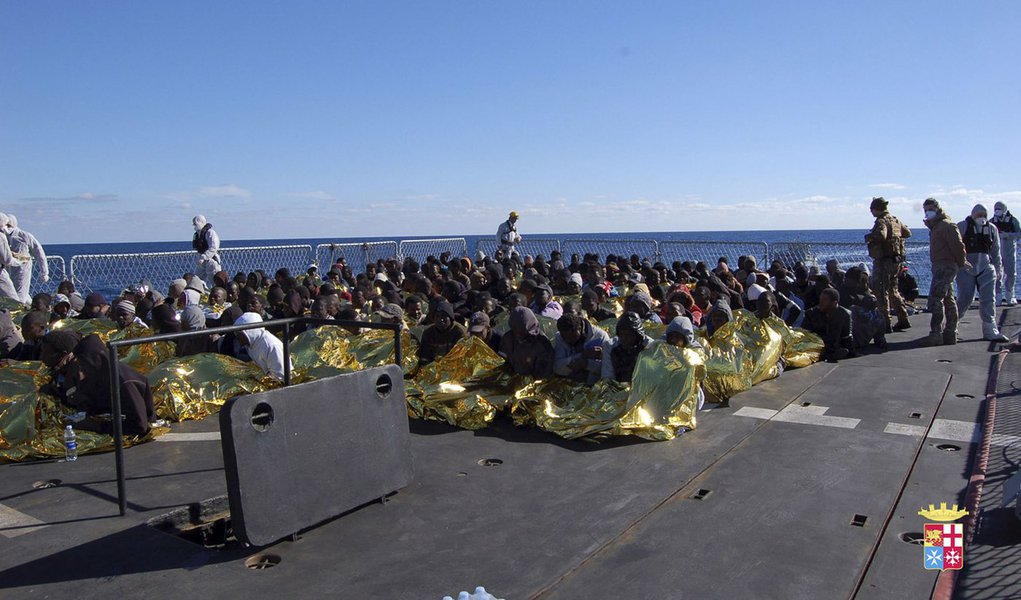 Migrants sit in a Marina Militare vessel during a rescue operation by Italian navy off the coast of the south of the Italian island of Sicily in this January 2, 2014 handout provided by the Italian Marina Militare. The Italian navy has rescued 233 mostly