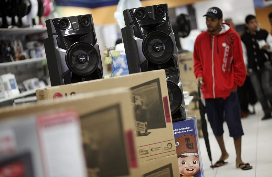 A man walks past speakers at a Casas Bahia store in Sao Paulo February 7, 2013. Brazil's inflation accelerated to the fastest rate in nearly eight years in January, raising bets of an interest rate hike this year that could complicate the government's dri