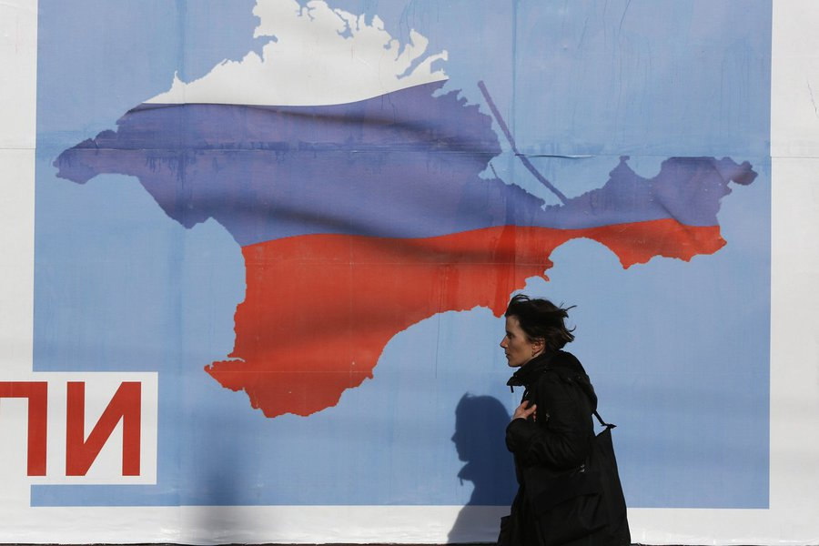 A woman walks by a poster in the Crimean port city of Sevastopol March 10, 2014. Crimea's parliament, dominated by ethnic Russians, voted to join Russia last week and set a referendum for March 16, escalating the crisis. REUTERS/Baz Ratner (UKRAINE - Tags