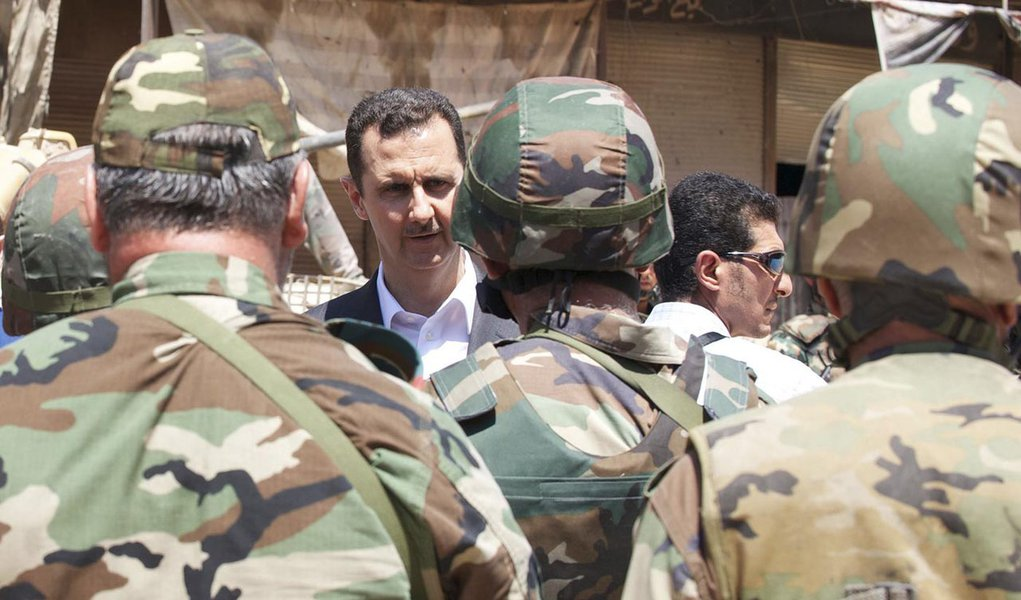 Syria's President Bashar al-Assad (C) chats with military personnel during his visit to a military site in the town of Daraya, southwest of Damascus, on the 68th anniversary of army day, in this handout photograph distributed by Syria's national news agen