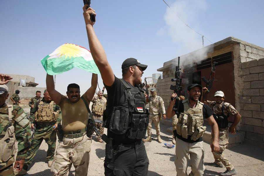 Combatentes curdos peshmerga comemoram tomada do controle de Sulaiman Pek, de militantes do Estado Islâmico, na cidade de Tikrit.  REUTERS/Youssef Boudlal