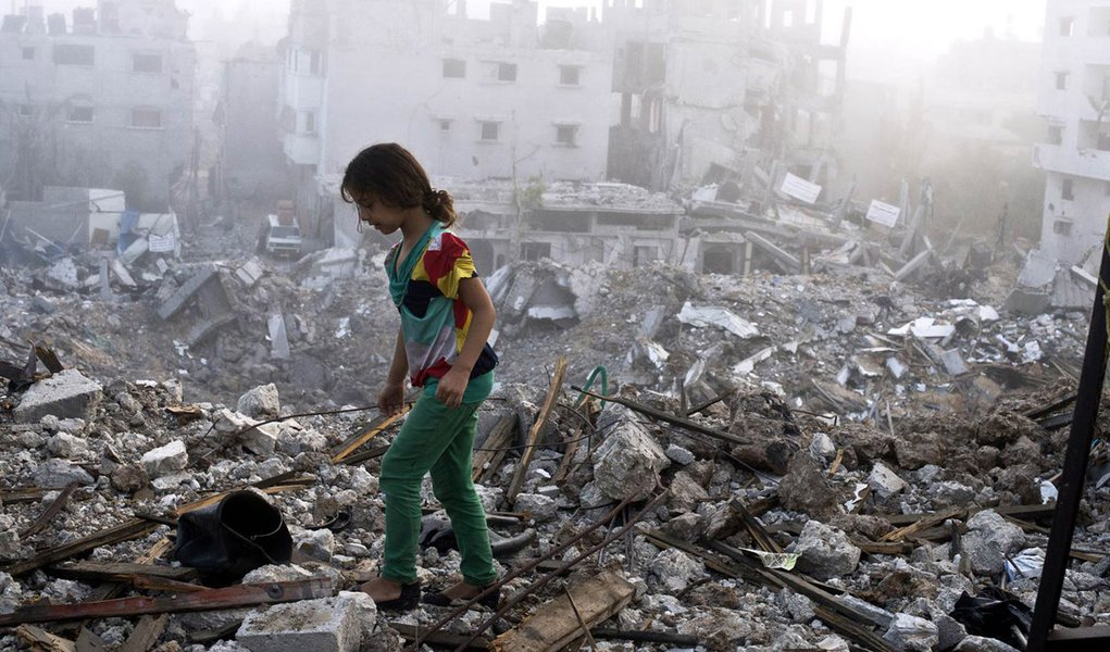 A Palestinian girl walks on the rubble strewn cieling of her family's home after she and other members of her family returned to their partially destroyed house early on August 27, 2014 in Gaza City's Shejaiya neighbourhood which was one of the hardest hi