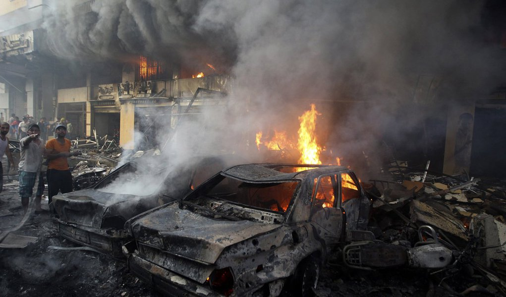 Supporters of Hezbollah try to extinguish a fire from burning cars at the site of a car bomb in Beirut's southern suburbs, August 15, 2013. The powerful car bomb struck the southern Beirut stronghold of Lebanon's militant Hezbollah group on Thursday, kill