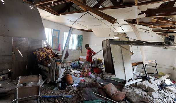 """Palestinian men inspect the damage at a UN school at the Jabalia refugee camp in the northern Gaza Strip after the area was hit by Israeli shelling on July 30, 2014. Israeli bombardments early on July 30 killed """"dozens"""" of Palestinians in Gaza, including"""