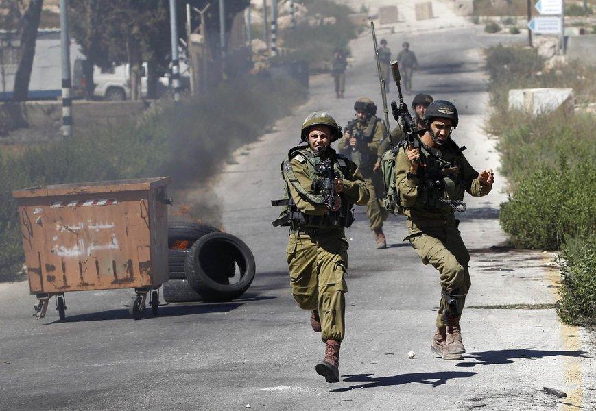 Soldados israelenses correm durante confrontos com manifestantes palestinos, perto de Ramallah, que protestavam contra a ofensiva de Israel em Gaza.  25/7/2014.  REUTERS/Mohamad Torokman