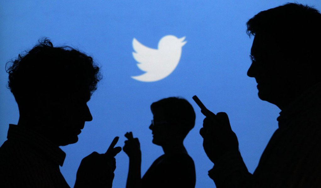 People holding mobile phones are silhouetted against a backdrop projected with the Twitter logo in this illustration picture taken in  Warsaw September 27, 2013. Twitter Inc, the eight-year-old online messaging service, gave potential investors their firs