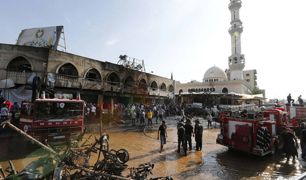Civil Defence members and residents gather at the site of one of two mosques hit by explosions in Lebanon's northern city of Tripoli, August 23, 2013. Twin explosions outside two mosques killed at least 27 people and wounded hundreds in apparently coordin