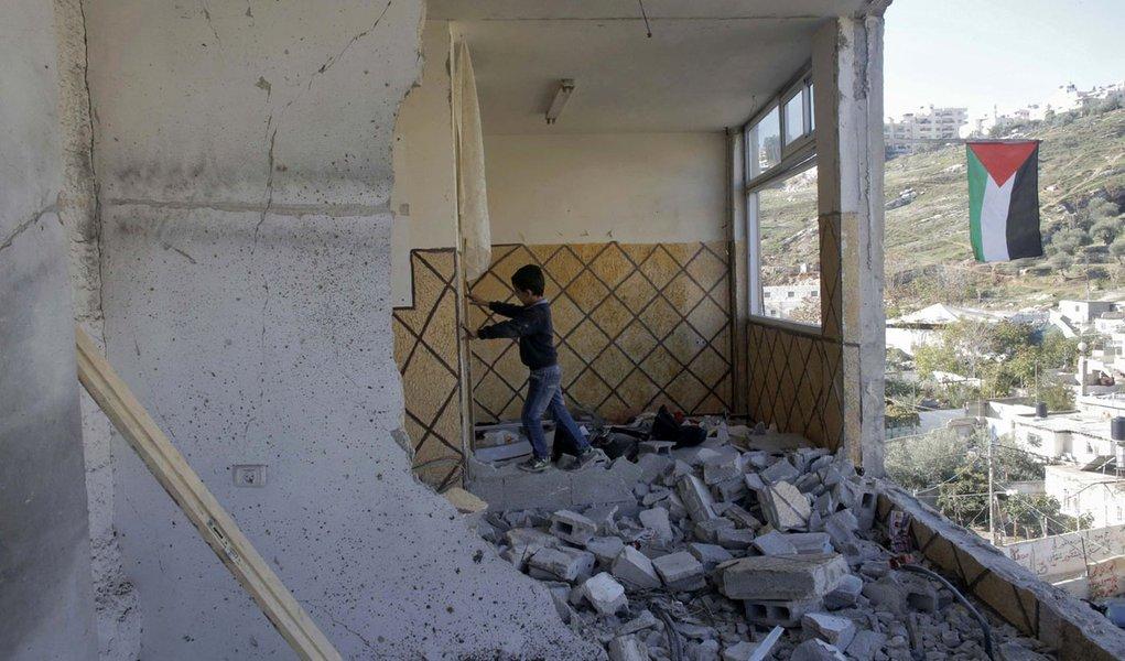 Menino palestino, familiar de Abdel-Rahman Shaloudi, sobre os escombros da casa destruída de Shaloudi em Jerusalém Oriental. 19/11/2014 REUTERS/Ammar Awad