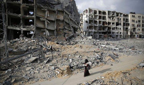 Palestina passa por prédios destruídos em Beit Lahiya, no norte da Faixa de Gaza. 03/08/2014 REUTERS/Finbarr O'Reilly