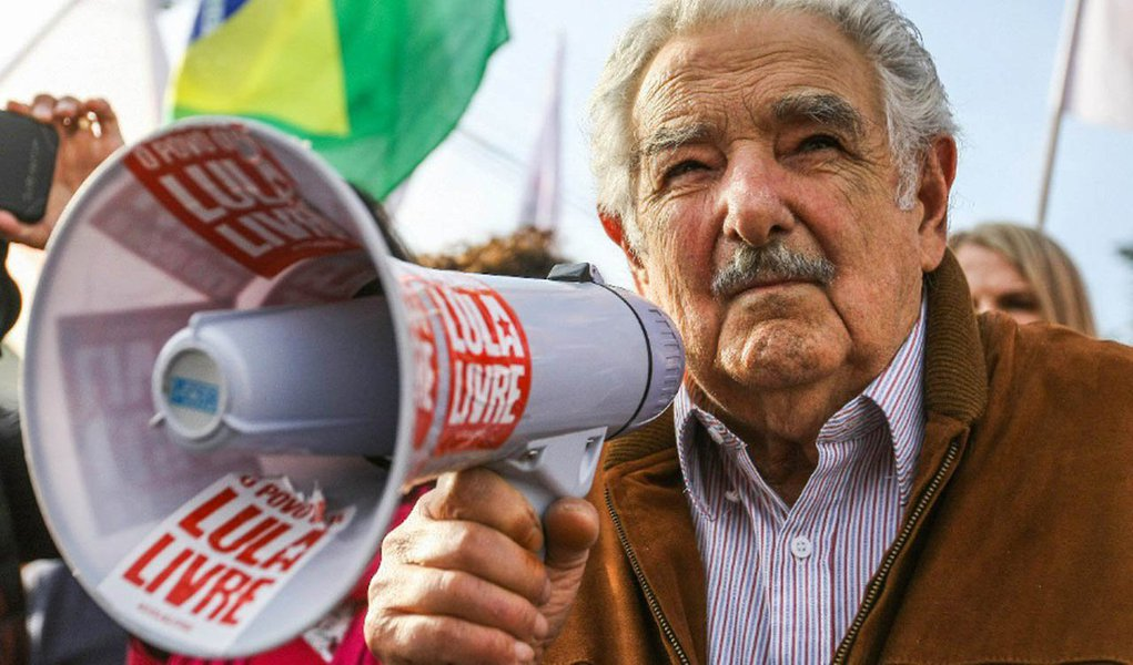 """Antes de visitar o ex-presidente Lula na prisão, o ex-presidente do Uruguai Jose Pepe Mujica fez um breve discurso à militância em frente à Polícia Federal em Curitiba; Mujica disse que veio visitar seu companheiro de luta; """"Adiante, companheiros, Lula somos todos. Todos os que têm problema na imensidão da América Latina, não se esqueçam"""", disse; assista sua fala"""