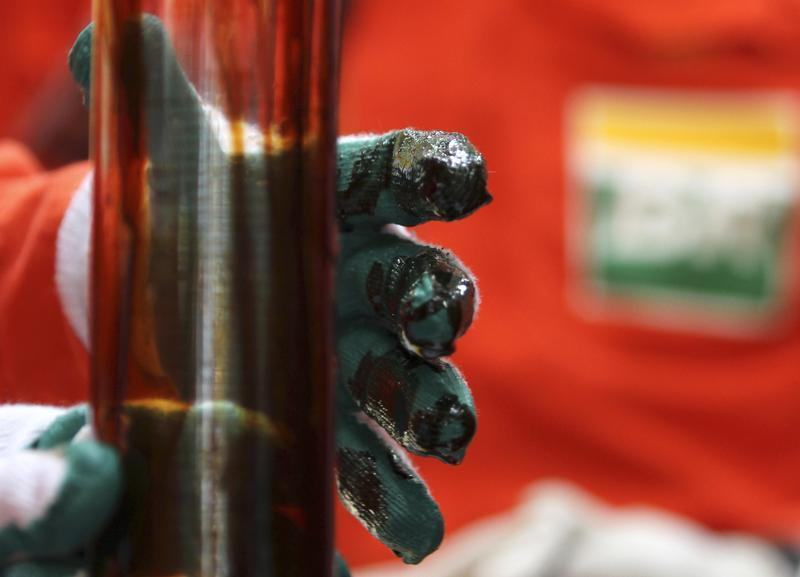 Operário checa amostra de óleo na plataforma de petróleo Cidade Angra dos Reis, no campo de Lula, Rio de Janeiro. A produção da Petrobras no Brasil e exterior somou 2,55 milhões de barris/dia de óleo equivalente em março, alta de 0,63 por cento ante o mês
