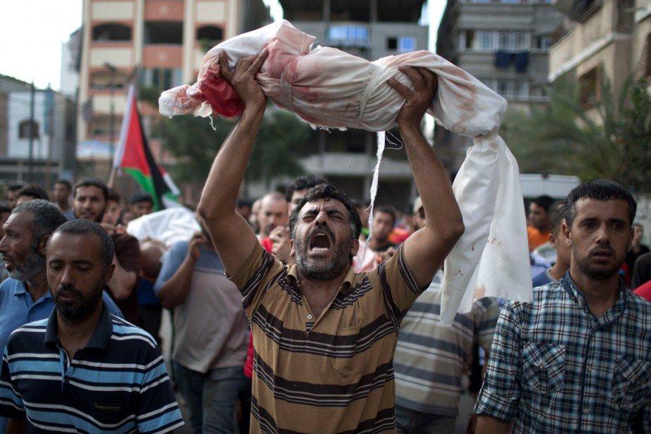 Palestino carrega corpo de crinça morta durante confronto com Exército de israel na faixa de Gaza