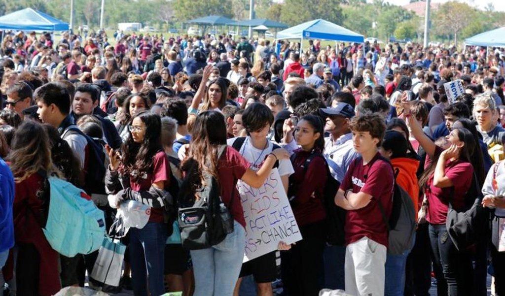"""Estudantes dos Estados Unidos deixaram as salas de aula aos milhares com cartazes e slogans como """"Queremos mudanças"""" em um protesto de costa a costa contra a violência das armas desencadeado por um massacre a tiros em uma escola secundária da Flórida no mês passado, quando 17 alunos e funcionários na escola secundária Marjory Stoneman Douglas de Parkland, na Flórida, foram assassinados; o massacre foi o mais recente de vários ocorridos em escolas e universidades dos EUA desde o ataque em Columbine"""
