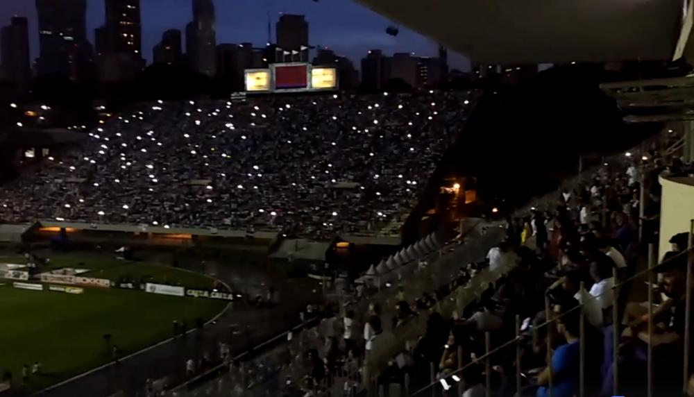 """No momento do apagão, que durou 50 minutos, neste domingo (4), durante jogo entre Santos e Corinthians, a torcida do Santos – única presento ao estádio – fez um coral com mais de 37 mil vozes contra a Rede Globo, que transmitia o espetáculo; """"Ô, tomar no c* Globo, tomar no c* Globo, tomar no c* Globo, ô""""; prefeito de São Paulo, João Doria, que estava no estádio, foi embora no momento do apagão; assista ao momento"""