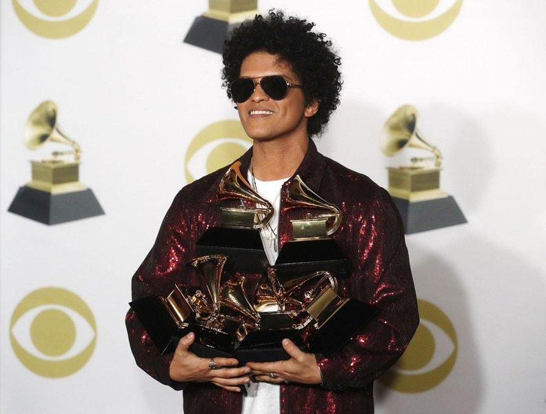 """O cantor Bruno Mars ganhou o principal prêmio do Grammy na noite de domingo, em outra vitória para a música pop sobre o rap, que atualmente é o gênero musical mais popular nos Estados Unidos; Mars ganhou em seis categorias, incluindo a música do ano por seu hit """"That's What I Like"""", e tanto gravação quanto álbum do ano com """"24K Magic""""; """"Essas músicas foram escritas com nada além de alegria, amor, e isso foi tudo que eu quis trazer com esse álbum, ver todo mundo dançando"""", disse Mars, de 32 anos"""