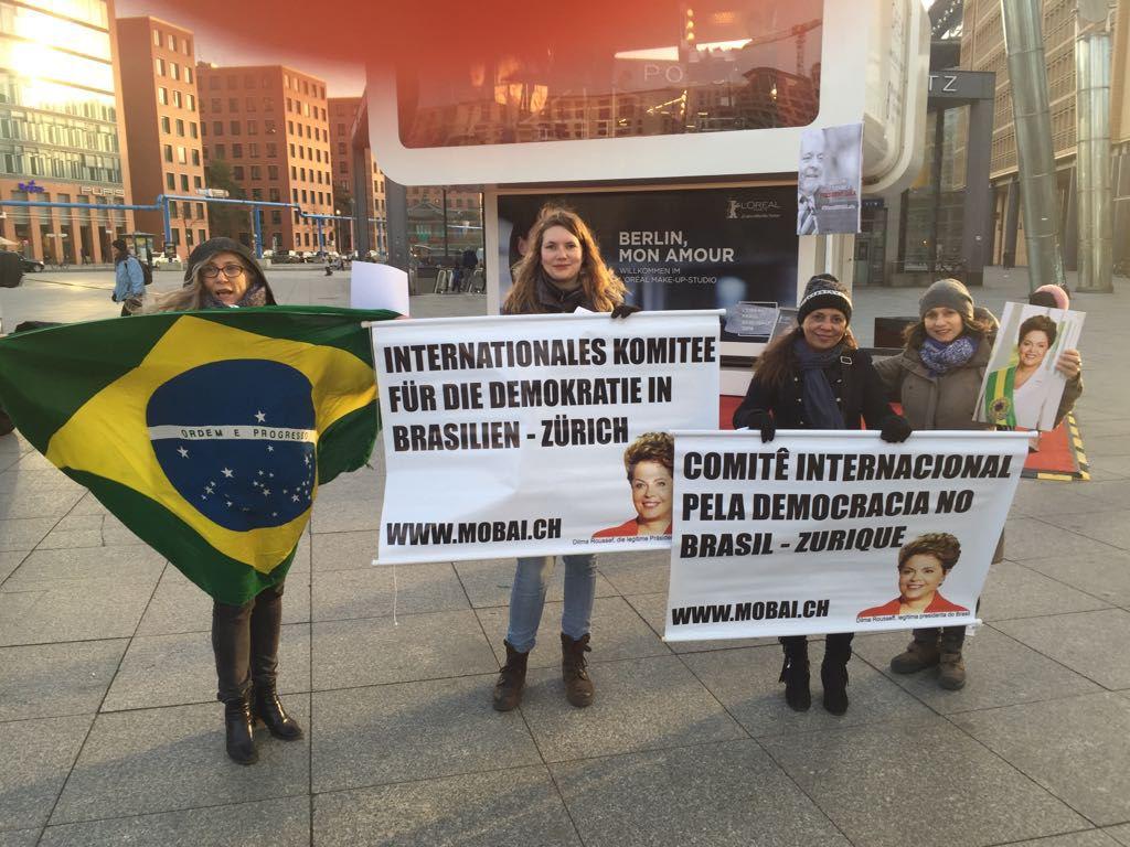 Um grupo de cerca de trinta manifestantes brasileiros se encontra em frente ao Potsdammerplatz, em Berlim, protestando pela democracia e contra os abusos do judiciário cometidos contra o ex-presidente Lula; nesta quarta-feira (21), acontece a estreia mundial do documentário O Processo, dirigido por Maria Augusta Ramos, que mostra os bastidores do golpe de 2016