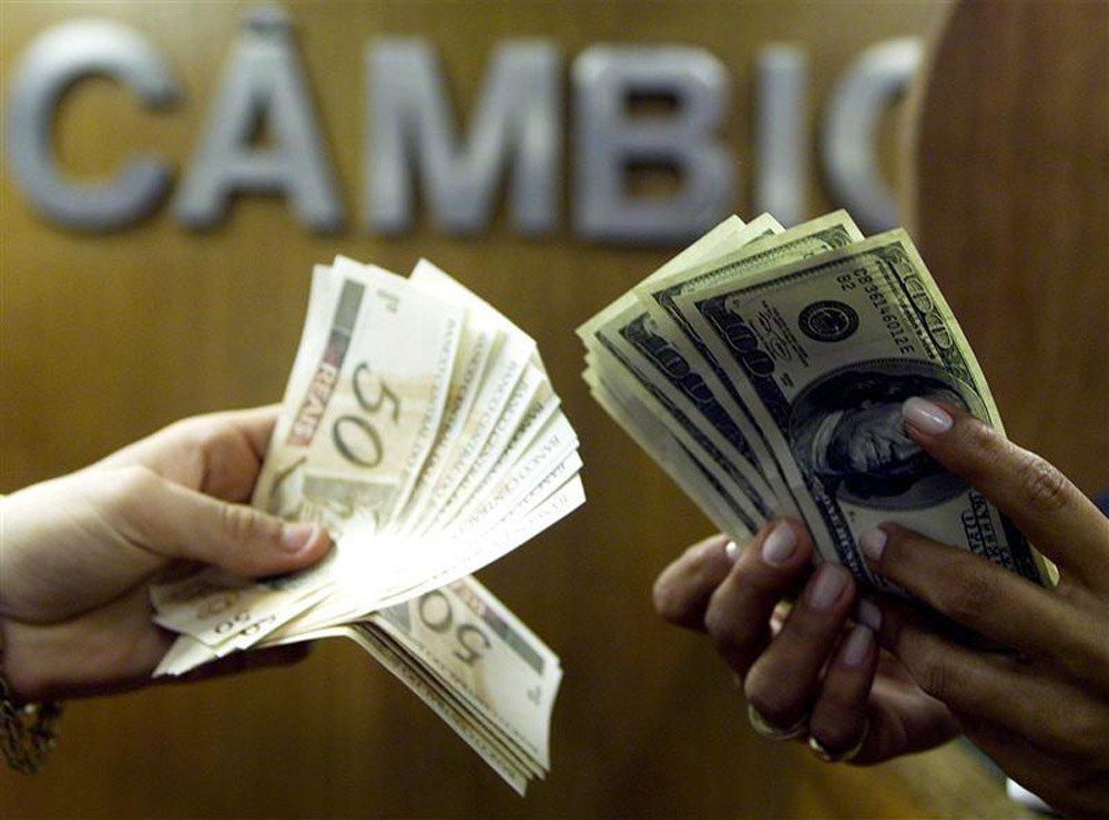 Brasileiro troca reais por dólares em corretora de câmbio no centro do Rio de Janeiro. O dólar fechou em baixa frente ao real nesta terça-feira, interrompendo sequência de duas altas, num pregão marcado por forte volatilidade e novamente com o Banco Centr