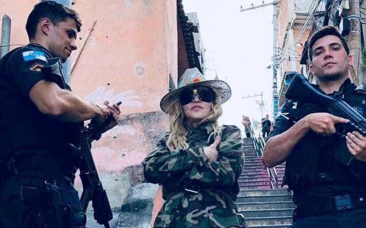 """O policial Raiff Medeiros negou que a Polícia Militar do Rio de Janeiro tenha escoltado a cantora Madonna em visita ao Morro da Providência, conforme acusou o Movimento Brasil Livre (MBL) em postagem nas redes sociais; """"Foi de surpresa"""", disse Raiff, que posou para foto com a artista norte americana; após a visita à comunidade na quarta-feira (25) Madonna publicou nas redes sociais uma foto ao lado de policiais armados com fuzis"""