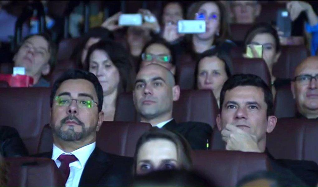 """Para a pré-estreia do filme da Lava Jato, uma equipe de segurança construiu um esquema para que delegados, policiais e procuradores pudessem chegar à sala onde seria feita a exibição sem causar agitação no cinema de um shopping de Curitiba; trajeto sem alarde foi feito pela força-tarefa nos bastidores do cinema, e deveria ter sido percorrido também pelo juiz Sergio Moro; mas o magistrado, acompanhado da esposa, fez questão de passar pelo """"tapete vermelho"""" acompanhado de seus próprios seguranças; Moro nega"""