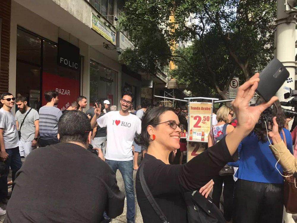 Chamado de 'esfihaço', um ato solidário reuniu centenas de cariocas em apoio ao refugiado sírio Mohammed Ali, vítima de xenofobia recentemente no Rio de Janeiro; o imigrante, que vende salgados árabes numa calçada em Copacabana, foi agredido verbalmente por um vendedor ambulante, que exigia que ele saísse do Brasil;a fila para comprar esfihas e quibes era formada por um número de 20 a 30 pessoas; Mohamed ficou o tempo todo ocupado, ora atendendo os pedidos, ora no caixa; ele só parava por poucos segundos para atender a pedidos de fotos dos clientes