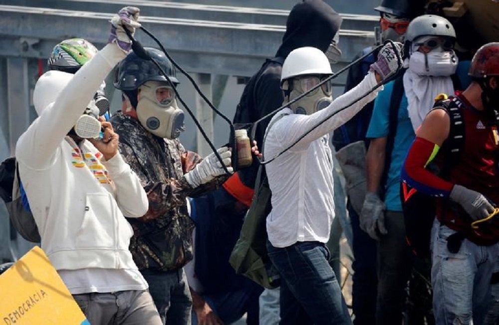 """Manifestantes lançam garrafas cheias de fezes, conhecidas como """"cocotov"""", durante protestos 10/05/2017 REUTERS/Carlos Garcia Rawlins"""