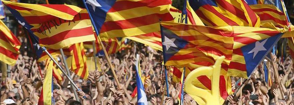 Pessoas erguem bandeiras da Catalunha durante manifestação pela independência em Barcelona. 19/10/2014. REUTERS/Albert Gea