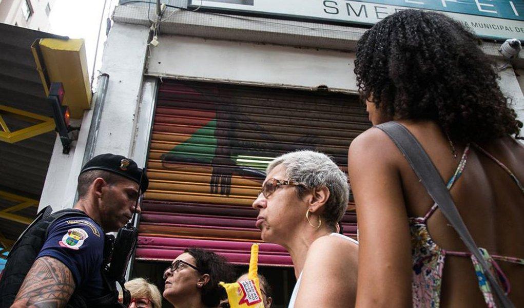 Dezenas de trabalhadores de educação, ligados à Prefeitura Municipal de Porto Alegre, fecharam a rua dos Andradas, em frente à Smed em protesto contra as novas diretrizes educacionais anunciadas por Nelson Marchezan Jr. esta semana; a manifestação aconteceu no mesmo horário que a professora da rede estadual e municipal, Maria Leonice de Deus, de 63 anos, tinha uma reunião marcada no prédio da Smed, como representante da Uampa; ao tentar entrar no local, a professora conta que foi barrada pela Guarda Municipal e foi encaminhada à delegacia de polícia