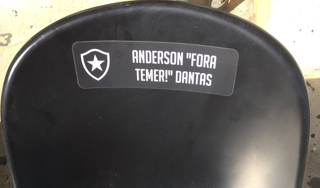 """Definitivamente, o futebol não é mais o """"ópio do povo""""; prova disso foi dada no Estádio Nilton Santos, no Rio, administrado pelo Botafogo; um torcedor do glorioso aderiu ao plano de customização do Niltão, que dá direito a colocar o nome na cadeira por R$ 50,00; de maneira inusitada o torcedor mandou personalizar com os seguintes dizeres: """"Anderson 'Fora, Temer' Dantas""""; ou seja, o amor ao clube serviu para Anderson demonstrar a sua insatisfação com o rumo que tem sido dado ao país pelo 'mordomo de filme de terror de quinta categoria'"""
