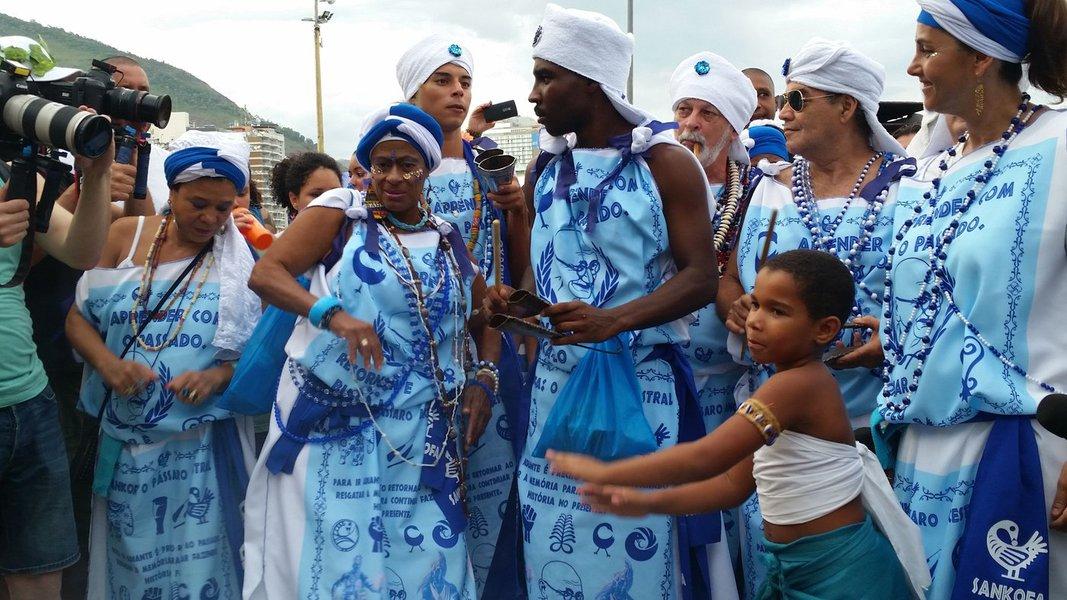 """Três grupos de afoxé do carnaval carioca se uniram e fizeram o desfile juntos hoje (27) em Copacabana. O Afoxé Filhos de Gandhi, pioneiro na cidade, chamou os """"filhos"""" Afoxé Raízes Africanas e Afoxé Ilê Alá para o cortejo de azul e branco pela Avenida Atlântida, que saiu por volta de 18h; fundado em 1951, o Filhos de Gandhi é o primeiro afoxé do Rio de Janeiro. Ele foi criado apenas dois anos depois do grupo de Salvador que leva o mesmo nome; """"Lá são só homens, aqui o homem continua o cérebro, mas a mulher é o coração. Somos pioneiros no Rio de Janeiro, é o primeiro afoxé da cidade"""", afirmaa diretora de produção do grupo carioca, Ya Regina"""