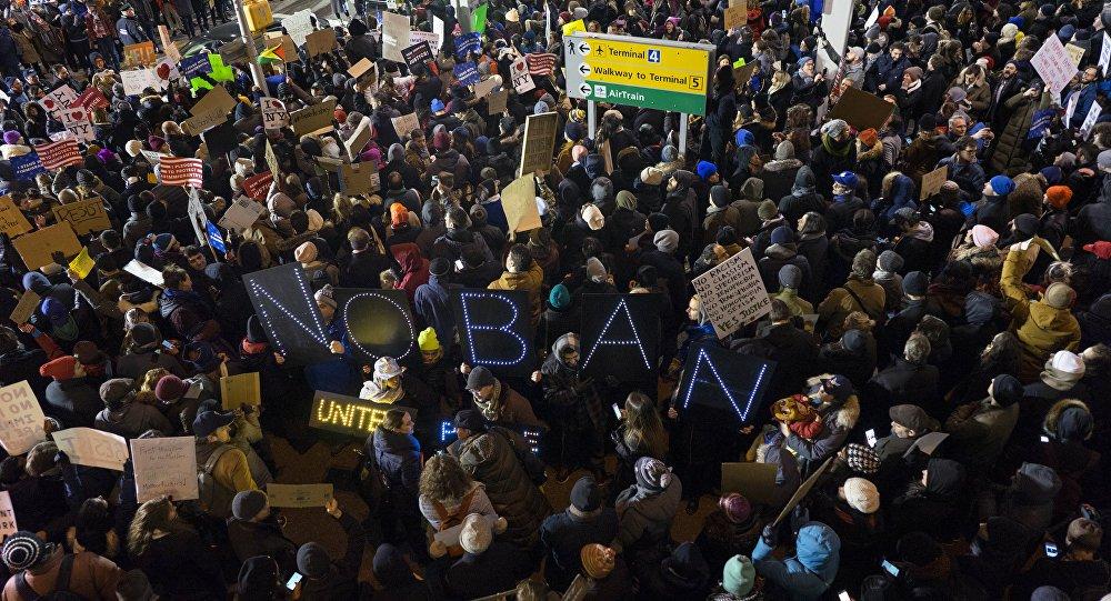 """Centenas de manifestantes se reuniram em frente ao aeroporto JFK, em Nova York, para protestar contra o decreto de Donald Trump que proíbe entrada de refugiados e imigrantes de sete países muçulmanos nos EUA; com faixas que diziam frases como """"Deixe meus amigos aqui"""" e """"Sem ódio, sem medo, refugiados são bem-vindos aqui"""", os manifestantes prestaram solidariedade aos imigrantes atingidos pelo decreto da administração Trump, que horas depois foi suspenso por decisão da Justiça Federal dos Estados Unidos"""