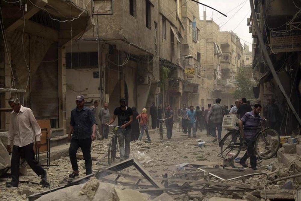 Pessoas em rua destruída por ataques aéreos, na cidade de Arbeen, Síria. 27/05/2015 REUTERS/Yousef Homs