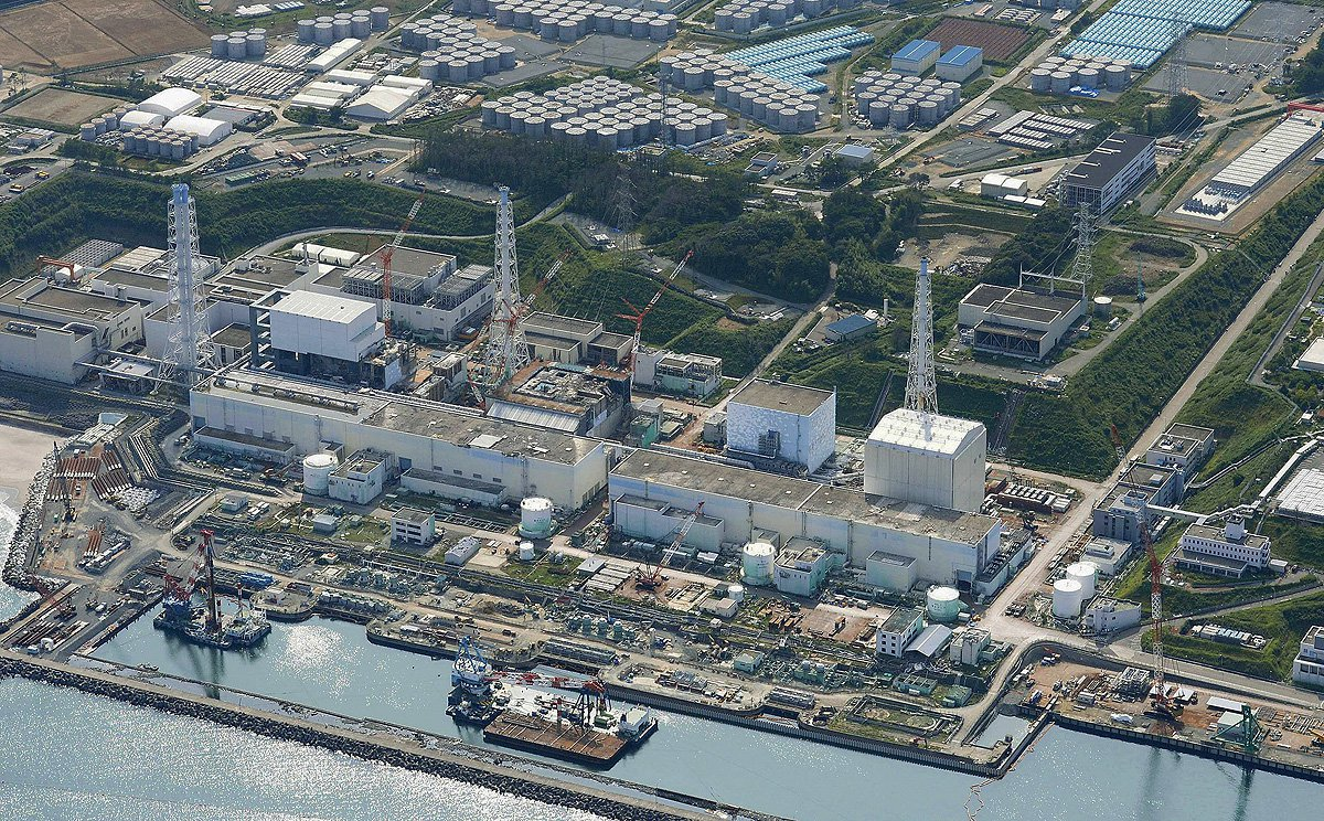 An aerial view shows the Tokyo Electric Power Co.'s (TEPCO) tsunami-crippled Fukushima Daiichi nuclear power plant and its contaminated water storage tanks (top) in Fukushima, in this photo taken by Kyodo August 31, 2013. Credit. REUTERS/Kyodo