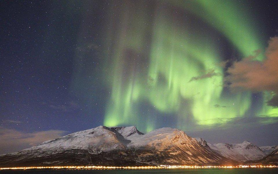 Vários membros de uma família de baleias-corcundas se encontram para dançar e brincar sob a luz mágica da aurora boreal.