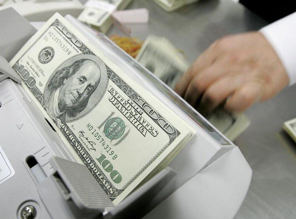 Um funcionário de um banco conta notas de cem dólares na sede do banco em Seul. O dólar chegou a recuar 2 por cento nesta quinta-feira, à casa dos 2,26 reais, após pesquisa mostrar queda na aprovação do governo da presidente Dilma Rousseff, num momento em
