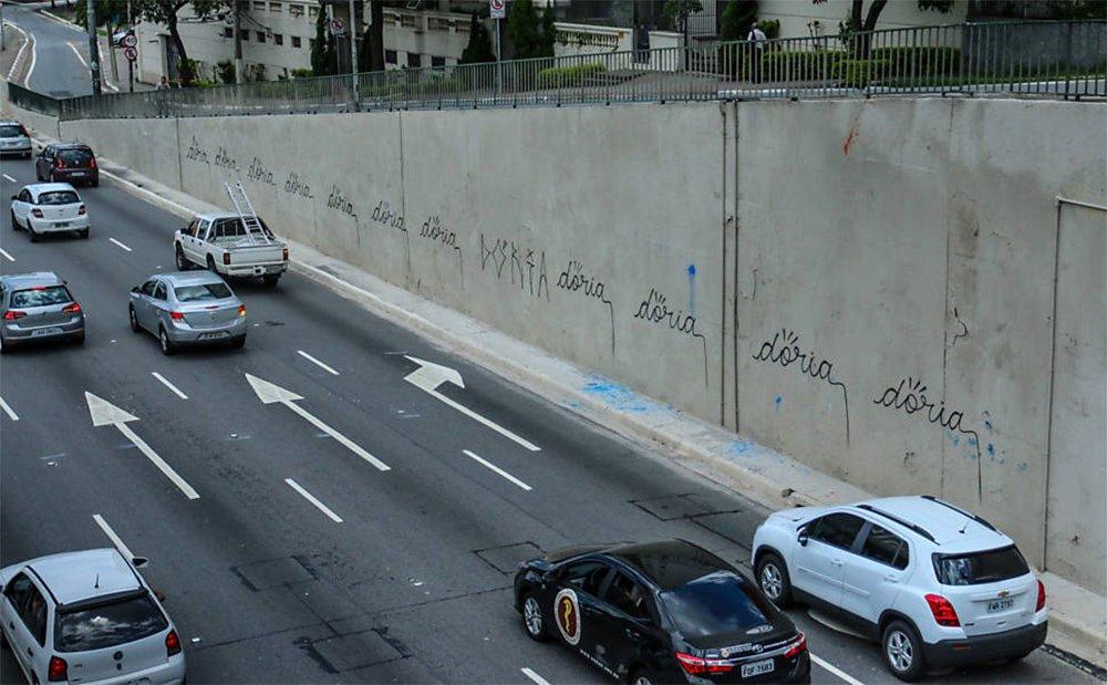 Após o prefeito de São Paulo, João Doria (PSDB), mandar cobrir de tinta cinza os muros da Avenida 23 de Maio, que estavam cheios de grafites, seu nome foi pichado repetidas vezes;funcionários da Prefeitura já pintaram novamente o muro, apagando as pichações