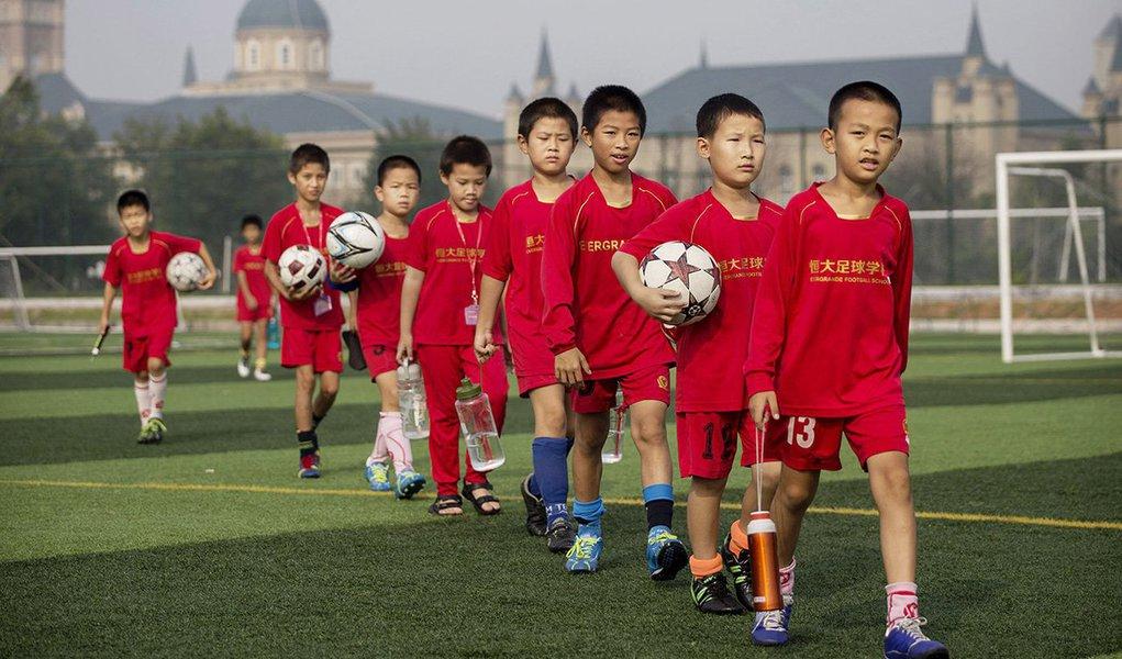 Wang Shijie, 11 anos, é uma estrela em ascensão entre os cerca de 3 mil alunos da enorme academia de futebol do Guangzhou Evergrande, no sul da China; ele quer se juntar à equipe nacional e ajudar o país a alcançar o sonho do presidente chinês Xi Jinping de ganhar a Copa do Mundo; com escolas como essa espalhadas por todo o país, a China prepara um exército de jovens jogadores que espera que possam ajudar a nação a sair de sua baixa posição entre os líderes do futebol mundial; a China atualmente ocupa o 84º lugar de 209 países, acima do Qatar e abaixo de equipes como Jordânia, Montenegro e Gabão
