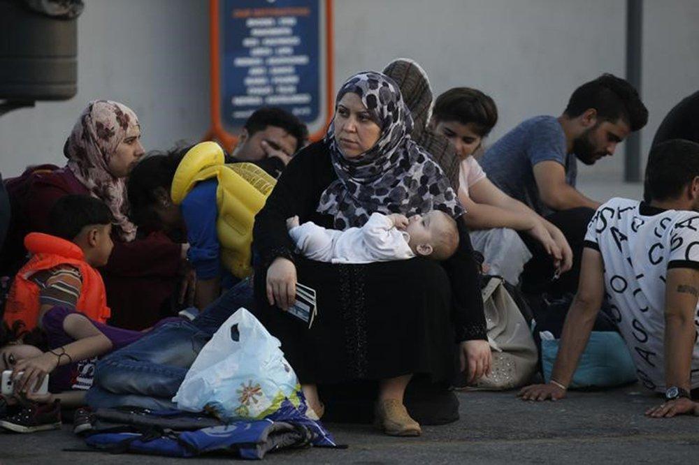 Refugiada síria, com bebê e passaportes, aguarda em porto da ilha grega de Kos. 17/82015 REUTERS/Alkis Konstantinidis