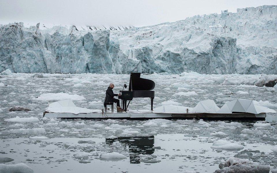 """Convidado pelo Greenpeace, o italiano Ludovico Einaudi, músico e compositor de fama mundial, estreou sua composição inédita """"Elegy for the Arctic"""", em uma performance sugestiva ao largo do glaciar Wahlenbergbreen, nas Ilhas Svalbard (Noruega), para a defesa do Ártico."""