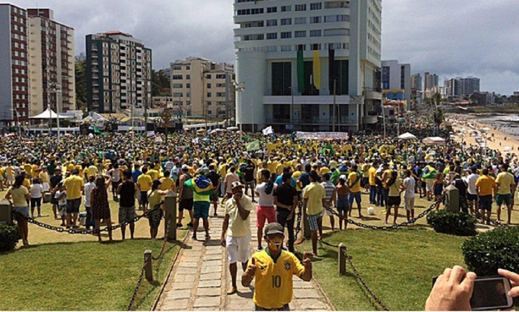 """Comandados por grupos nas redes sociais, cerca de 4 mil manifestantes (segundo cálculos da Polícia Militar) começaram a se reunir por volta das 9 horas desta manhã ensolarada de domingo, no Porto da Barra, em Salvador, para protestarem contra o governo da presidente Dilma Rousseff; com gritos de """"Fora, Dilma!"""", eles se vestiam, em sua maioria, com roupas nas cores verde e amarelo e pintavam o rosto com faixas nas mesmas cores"""