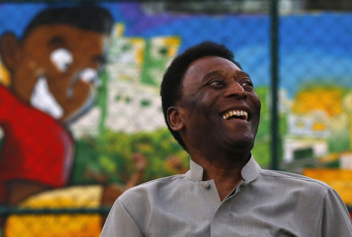 Brazilian soccer legend Pele laughs during the inauguration of a refurbished soccer field at the Mineira slum in Rio de Janeiro September 10, 2014. The soccer pitch was refurbished by Anglo-Dutch oil company Royal Dutch Shell using underground tiles which