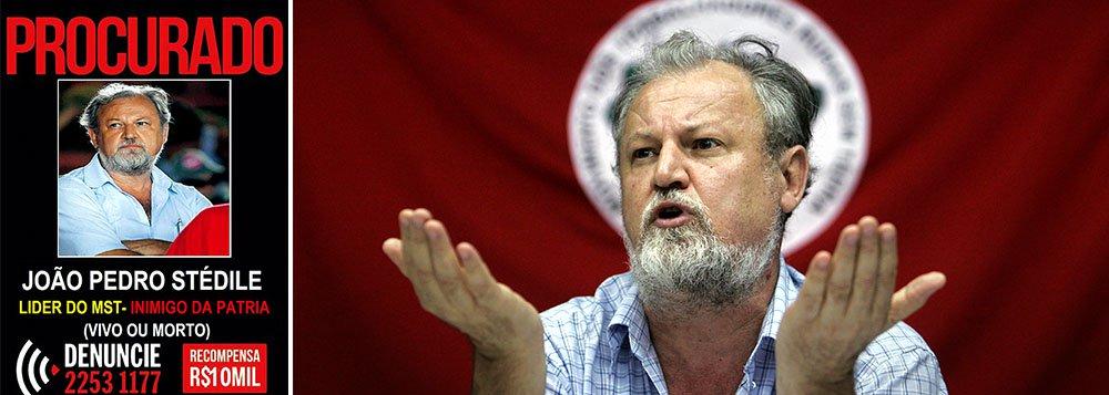 """Uma imagem que circula no Facebook – divulgada por um guarda municipal aposentado de Macaé (RJ) – coloca João Pedro Stédile, líder do MST, como um criminoso procurado pela polícia e refere-se a ele como """"Inimigo da Pátria""""; """"cartaz"""" oferece uma """"recompensa"""" de R$ 10 mil e diz que ele é buscado """"Vivo ou Morto""""; caso será denunciado à Polícia Federal, ao Ministério da Justiça e ao Facebook"""