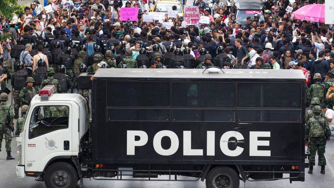 Junta militar da Tailândia manteve fora das ruas muitos dos milhares de soldados e policiais que preparou para lidar com protestos em Bangcoc neste domingo, uma vez que o número de pessoas que fazem manifestações públicas contra o golpe de 22 de maio diminuiu; militares reprimiram duramente os dissidentes pró-democracia desde a derrubada do primeiro-ministro Yingluck Shinawatra, no mês passado, buscando silenciar críticas e cortar protestos pela raiz