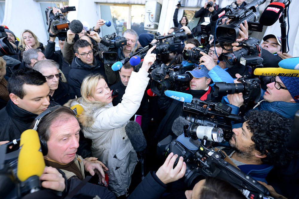 Michael Schmacher's manager, Sabine Khem (C), speaks to journalists in front of the Grenoble CHU hospital on January 1st, 2014 where the Formula One legend spent a third night in hospital in an induced coma after an off-piste skiing accident in the French