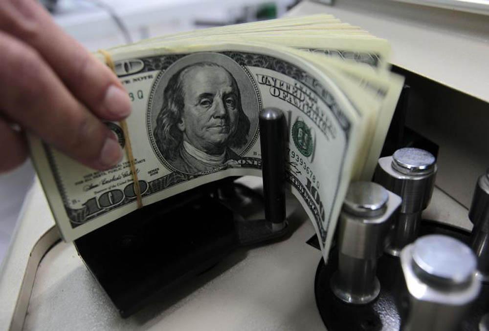 Um funcionário de banco conta notas de cem dólares em Bangcoc. O fluxo cambial, entrada e saída e moeda estrangeira do país, ficou negativo em 1,95 bilhões de dólares na semana passada, fazendo com que fevereiro como um todo fechasse no vermelho, com défi