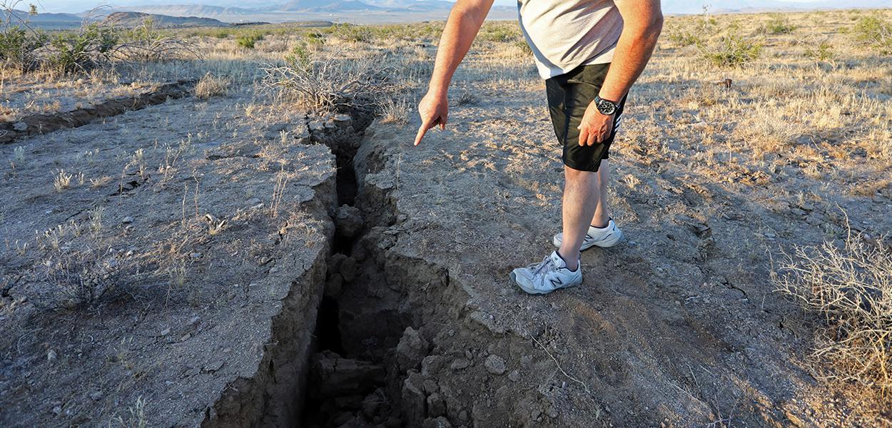 Homem observa fissura aberta por terremoto em deserto da Califórnia04/07/2019REUTERS/David McNew