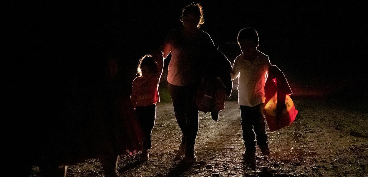 Mulher de Honduras com dois filhos é acompanhada por agente de fronteira dos EUA
