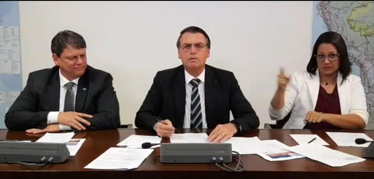O presidente Jair Bolsonaro faz transmissão ao vivo ao lado do ministro da Infraestrutura, Tarcísio Gomes de Freitas, e da intérprete de libras, Elizângela Castelo Branco.