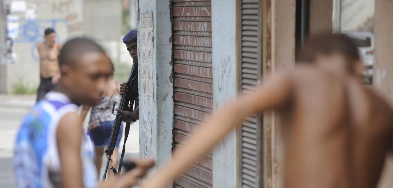 Policial armado observa jovens negros na favela